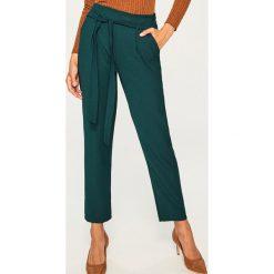 Spodnie z wiązanym paskiem - Khaki. Brązowe spodnie materiałowe damskie Reserved. W wyprzedaży za 49.99 zł.