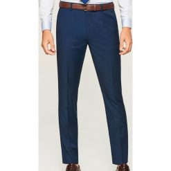 Spodnie garniturowe z tkaniny strukturalnej - Granatowy. Niebieskie eleganckie spodnie męskie Reserved, z tkaniny. Za 149.99 zł.