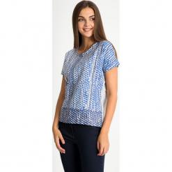 Szara bluzka w niebieskie kółka QUIOSQUE. Niebieskie bluzki damskie QUIOSQUE, z nadrukiem, z bawełny, biznesowe, z dekoltem w łódkę, z krótkim rękawem. W wyprzedaży za 59.99 zł.