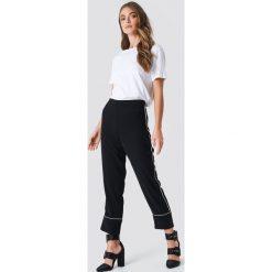 NA-KD Trend Spodnie z kontrastową lamówką - Black. Czarne spodnie materiałowe damskie NA-KD Trend, w paski. Za 202.95 zł.