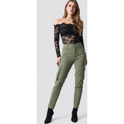Pamela x NA-KD Spodnie z wysokim stanem Army - Green. Zielone spodnie materiałowe damskie Pamela x NA-KD. Za 202.95 zł.