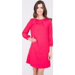 Malinowa trapezowa sukienka QUIOSQUE. Różowe sukienki damskie QUIOSQUE, z materiału, z kopertowym dekoltem. W wyprzedaży za 59.99 zł.