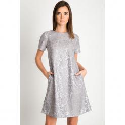 Srebrna sukienka z koronką QUIOSQUE. Szare sukienki damskie QUIOSQUE, w koronkowe wzory, z koronki, eleganckie, z kopertowym dekoltem, z krótkim rękawem. Za 219.99 zł.