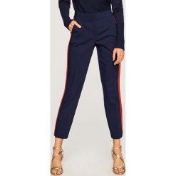 Spodnie z lampasem - Granatowy. Niebieskie spodnie materiałowe damskie Reserved. Za 99.99 zł.