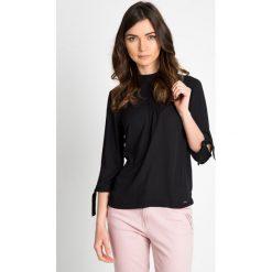 Elegancka czarna bluzka z wiązanymi rękawami  QUIOSQUE. Czarne bluzki damskie QUIOSQUE, z tkaniny, eleganckie, z dekoltem na plecach. W wyprzedaży za 69.99 zł.