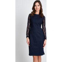 Granatowa sukienka z koronkowymi rękawami QUIOSQUE. Szare sukienki damskie QUIOSQUE, w koronkowe wzory, z dzianiny, eleganckie, z kopertowym dekoltem, z długim rękawem. W wyprzedaży za 69.99 zł.