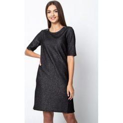Czarna błyszcząca sukienka z zamkami na ramionach QUIOSQUE. Czarne sukienki damskie QUIOSQUE, z dzianiny, biznesowe, z dekoltem na plecach, z krótkim rękawem. W wyprzedaży za 119.99 zł.