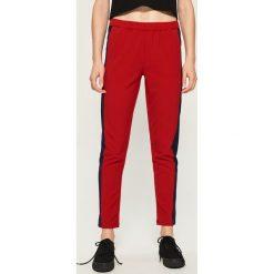 Spodnie slim fit z pasami - Czerwony. Spodnie materiałowe damskie marki DOMYOS. W wyprzedaży za 29.99 zł.