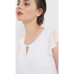 Koszulka z błyszczącym detalem. Białe bluzki damskie Orsay, z aplikacjami, z dzianiny, z dekoltem na plecach. Za 69.99 zł.