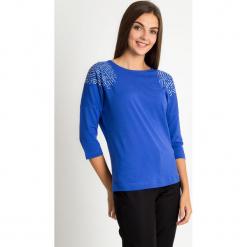 Niebieska bluzka z ozdobnymi ramionami QUIOSQUE. Niebieskie bluzki damskie QUIOSQUE, z nadrukiem, z bawełny, biznesowe, z dekoltem w łódkę. W wyprzedaży za 49.99 zł.
