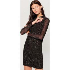 Sukienka z połyskującą aplikacją - Czarny. Czarne sukienki damskie Mohito, z aplikacjami. Za 149.99 zł.