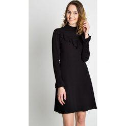 Czarna elegancka sukienka z falbaną na dekolcie BIALCON. Czarne sukienki damskie BIALCON, eleganckie, z falbankami. Za 335.00 zł.