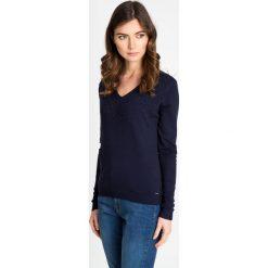 Granatowy sweter z kamieniami QUIOSQUE. Niebieskie swetry damskie QUIOSQUE, z dzianiny, z dekoltem w serek. W wyprzedaży za 79.99 zł.