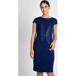 Granatowa sukienka z błyszczącym wzorem QUIOSQUE. Czarne sukienki damskie QUIOSQUE, z tkaniny, eleganckie, z kopertowym dekoltem. W wyprzedaży za 109.99 zł.