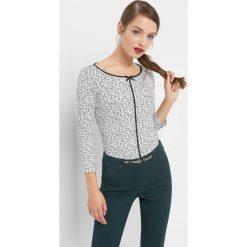 Koszulka w kwiaty z lamówką. Białe bluzki damskie Orsay, w kwiaty, z bawełny, z kokardą. Za 69.99 zł.