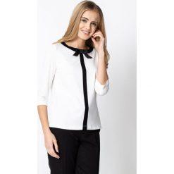 Biała bluzka z czarną kokardą QUIOSQUE. Białe bluzki damskie QUIOSQUE, z dzianiny, biznesowe, z kokardą. Za 129.99 zł.