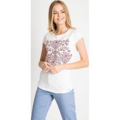 Biała bluzka z kwiatowym nadrukiem QUIOSQUE. Białe bluzki damskie QUIOSQUE, z nadrukiem, z bawełny, biznesowe, z dekoltem w łódkę, z krótkim rękawem. W wyprzedaży za 19.99 zł.