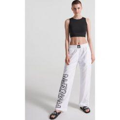 Sportowe spodnie z napisami - Biały. Spodnie dresowe damskie Reserved, z napisami. W wyprzedaży za 39.99 zł.