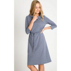 Niebieska sukienka w mikrowzór z wiązaniem QUIOSQUE. Niebieskie sukienki damskie QUIOSQUE, z dzianiny, biznesowe, z klasycznym kołnierzykiem, z długim rękawem. W wyprzedaży za 99.99 zł.