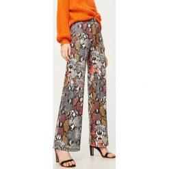 Spodnie we wzory - Wielobarwn. Brązowe spodnie materiałowe damskie Reserved. Za 119.99 zł.