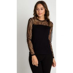 Czarna bluzka z koronkowymi rękawami BIALCON. Czarne bluzki damskie BIALCON, w koronkowe wzory, z koronki, eleganckie. Za 99.00 zł.