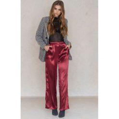 NA-KD Party Metaliczne spodnie z rozszerzaną nogawką - Red. Czerwone spodnie materiałowe damskie NA-KD Party, z poliesteru. W wyprzedaży za 81.18 zł.