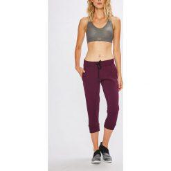 Under Armour - Spodnie. Szare spodnie sportowe damskie Under Armour, z aplikacjami, z bawełny. W wyprzedaży za 169.90 zł.