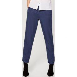 Luźne spodnie ze ściągaczem - Niebieski. Niebieskie spodnie materiałowe damskie Mohito. Za 79.99 zł.