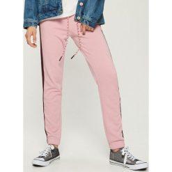 Spodnie dresowe z lampasami - Różowy. Czerwone spodnie dresowe damskie Sinsay, z dresówki. Za 49.99 zł.