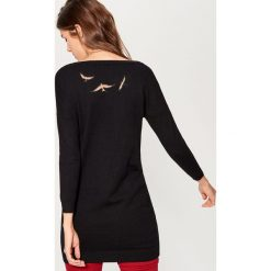 Długi sweter z aplikacją na plecach - Czarny. Czarne swetry damskie Mohito, z dekoltem na plecach. W wyprzedaży za 59.99 zł.