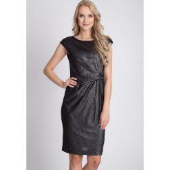 Czarna metaliczna sukienka QUIOSQUE. Czarne sukienki damskie QUIOSQUE, z dzianiny, eleganckie, z kopertowym dekoltem. W wyprzedaży za 59.99 zł.