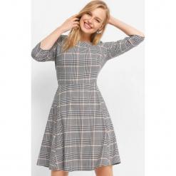 Rozkloszowana sukienka w kratę. Szare sukienki damskie Orsay, z bawełny, klasyczne, z dekoltem na plecach. Za 139.99 zł.