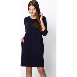 Granatowa błyszcząca sukienka wiązana na plecach QUIOSQUE. Szare sukienki damskie QUIOSQUE, z dzianiny, biznesowe, z dekoltem na plecach, z długim rękawem. W wyprzedaży za 159.99 zł.