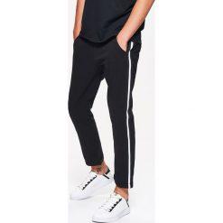 Materiałowe spodnie CHINO SLIM z lampasem - Czarny. Spodnie materiałowe męskie marki House. W wyprzedaży za 49.99 zł.