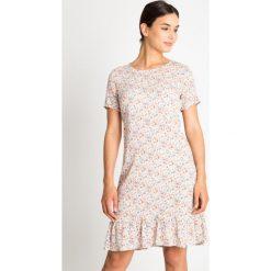 Sukienka w kwiatki z falbaną QUIOSQUE. Białe sukienki dla dziewczynek QUIOSQUE, w kolorowe wzory, z tkaniny, wakacyjne, z długim rękawem. W wyprzedaży za 79.99 zł.