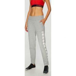 Under Armour - Spodnie. Szare spodnie sportowe damskie Under Armour, z nadrukiem, z bawełny. W wyprzedaży za 149.90 zł.