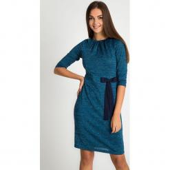 Niebieska błyszcząca sukienka z kokardą QUIOSQUE. Niebieskie sukienki damskie QUIOSQUE, z materiału, eleganckie, z dekoltem w łódkę, z długim rękawem. Za 199.99 zł.