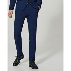 Spodnie garniturowe slim fit - Granatowy. Niebieskie eleganckie spodnie męskie Reserved. Za 149.99 zł.