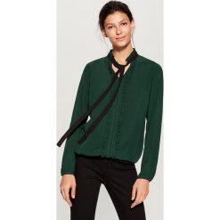 Koszula z kontrastowym wiązaniem - Khaki. Brązowe koszule damskie Mohito, z kontrastowym kołnierzykiem. W wyprzedaży za 49.99 zł.