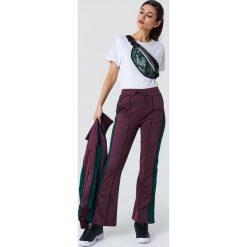 NA-KD Spodnie sportowe z rozcięciem - Purple. Fioletowe spodnie sportowe damskie NA-KD, w paski, z poliesteru. Za 161.95 zł.