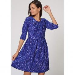 Sukienka w kolorze niebieskim. Niebieskie sukienki damskie TrakaBarraka, z falbankami. W wyprzedaży za 119.95 zł.