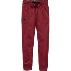 Spodnie sportowe trykotowe bonprix ciemnoczerwony. Czerwone spodnie sportowe męskie bonprix, z nadrukiem. Za 59.99 zł.
